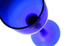 Blue wine glass. A blue wine glass lit from below on a white background Stock Image