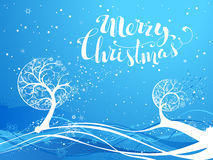 Blue winter tree background. Ornate trees with snowflakes on blue waves background. Hand-written Merry Christmas. There is copy space for your text Stock Image