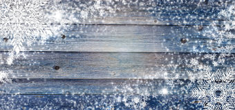 Blue winter wooden background with snowflakes around. Christmas, New Year card with copy space in the center