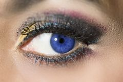 Blue woman eye. Macro photography of a woman blue eye. The eye have a party make up. Horizontal shot Stock Photos