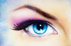 Blue woman eye with violet and pink day makeup. Color painting Royalty Free Stock Images