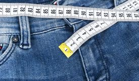 A blue woman jeans and ruler, concept of diet and weight loss. Jeans with measuring tape. Healthy lifestyle, dieting, fitness. Stock Photos