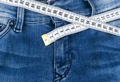 A blue woman jeans and ruler, concept of diet and weight loss. Jeans with measuring tape. Healthy lifestyle, dieting, fitness. Stock Image