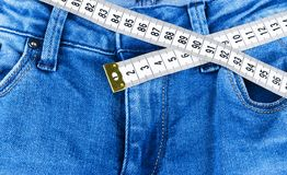 A blue woman jeans and ruler, concept of diet and weight loss. Jeans with measuring tape. Healthy lifestyle, dieting, fitness. Royalty Free Stock Images