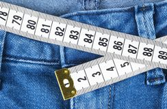 A blue woman jeans and ruler, concept of diet and weight loss. Jeans with measuring tape. Healthy lifestyle, dieting, fitness. Royalty Free Stock Photo