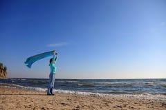 Woman and shawl at sea shore Stock Image