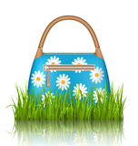 Blue woman spring bag with chamomiles flowers in grass lawn with Royalty Free Stock Image