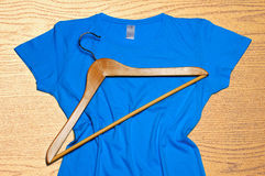 Blue women's t-shirt and wooden hanger lie on wooden background Royalty Free Stock Photos
