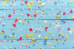 Blue wood background with scattered party confetti. Blue wood background with scattered colorful party confetti with heart shapes in a closeup full frame stock images