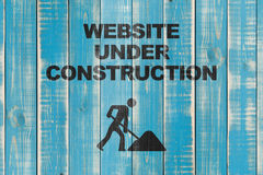 Website under construction. A blue wood background with the text 'Website under construction royalty free stock photo