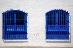 Blue wood   couple of window in a white wall arrecife lanzarote. Spain Stock Photos