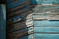 Blue wood door made of boards with metal handle. Blue painted wooden peeled off door made of boards with metal handle Royalty Free Stock Photography