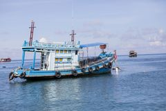 Blue wood fishery boat floating on harbor port Stock Photography