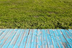 Blue wood planks. And green grass Royalty Free Stock Images