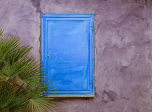 Blue wood shutter on purple wall Stock Photos
