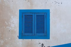 Blue wood window on an old dirty wall. Funchal, Madeira island, Portugal royalty free stock images