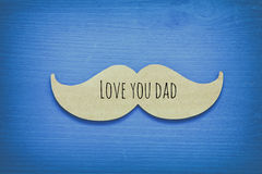 Blue wooden background and paper mustache. fathers day concept Royalty Free Stock Photo