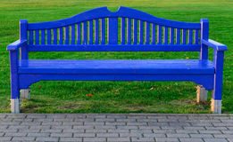 Blue wooden bench on green grass Stock Images