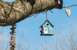 Blue wooden bird house in a tree in the park.  stock photography