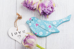 Blue wooden bird with purple tulips and white heart stock photography