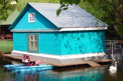 Blue wooden boat house and a white swan near lake Royalty Free Stock Images