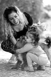 Mother, her child and dog. A mother playing with her daughter and female dog Stock Photo