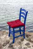 Blue wooden chair with red cushion Stock Photos