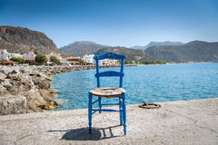 Blue wooden chair at sea coastline Royalty Free Stock Photos