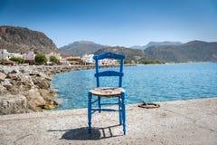 Blue wooden chair at sea coastline. On Crete island Royalty Free Stock Photos