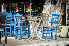 Blue wooden chairs and table at traditional Greek tavern Royalty Free Stock Photos
