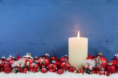 Blue wooden christmas background with a white candle and red bal royalty free stock photography