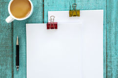 Blue wooden desk table with paper reams and cup of coffee. Top view with copy space, flat lay Stock Image