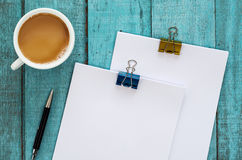 Blue wooden desk table with paper reams, pen and cup of coffee. Top view with copy space, flat lay Royalty Free Stock Images