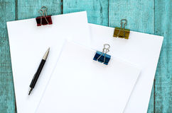 Blue wooden desk table with paper reams and pen. Stock Photography