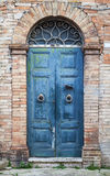 Blue wooden door with arch in old brick wall Stock Photos