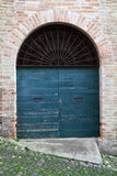Blue wooden door with arch in old brick wall Stock Images