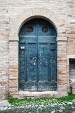 Blue wooden door with arch in old stone wall Royalty Free Stock Photography