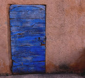 Blue wooden door embedded in a red wall in Roussillion. Blue door against red wall in France Royalty Free Stock Photos