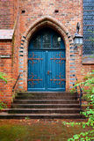 Blue wooden door, entrance to an old brick church Stock Photography