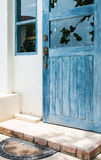 Blue wooden door with old doormat Royalty Free Stock Photo