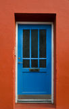 Blue wooden door on a red wall Royalty Free Stock Photos