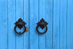 Blue wooden door with round handles. Bright blue wooden door with round handles royalty free stock photography