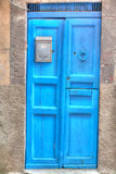 Blue wooden door in a rustic wall Royalty Free Stock Photography