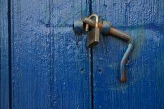 Blue wooden door with rusty open padlock (unlocked) Royalty Free Stock Image