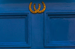 Blue wooden door to house with a brass knocker in the shape of h stock photos