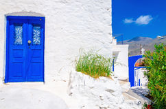 Blue wooden door, white wall and flowers in Greece Royalty Free Stock Image
