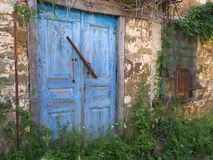 Blue Wooden Doors on Old Stone Greek Village House. A very old stone and mud owner built built Greek village house, with faded and flaking blue painted wooden Stock Photography