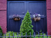 Blue wooden doors on a red brick building with green fir trees. Stock Photography