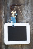 Blue wooden easter bunny sitting on a blackboard and makes adver Royalty Free Stock Image