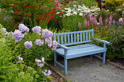 Blue wooden garden bench. Old blue wooden garden bench in colorful summer garden Stock Photo
